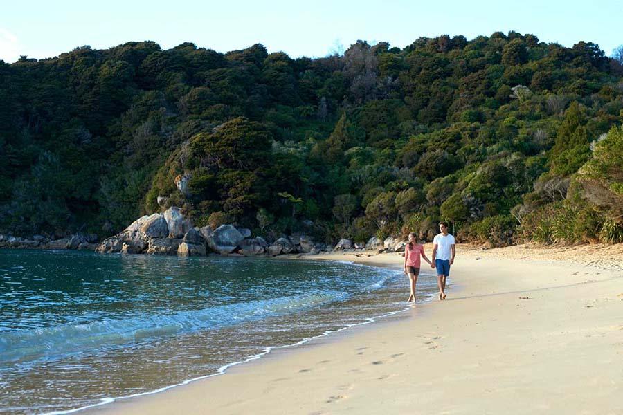 A couple on the beach in Abel Tasman National Park, New Zealand